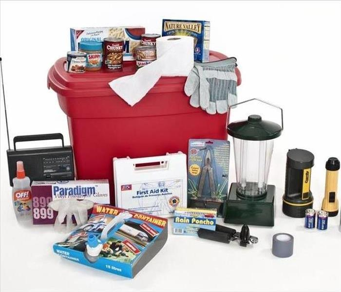 A red emergency tote with a medical kit and other assorted emergency items.